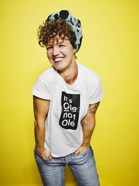Доросла жінка в модному випадковому одязі з головою посміхається дивлячись геть, стоячи з руками в кишені на жовтому фоні — стокове фото