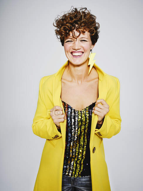 Cheerful woman with sequin top and lightning earring smiling and adjusting stylish yellow coat against gray background — Stock Photo