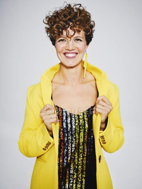 Весела жінка з секвеніром і блискавкою посміхається і налаштовує стильно-жовте пальто на сірий фон — стокове фото