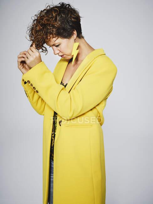Дорослі самиці в стильному жовтому пальто і з блискавичним сережкою за допомогою гребінця стискають кучеряве волосся на сірому тлі — стокове фото