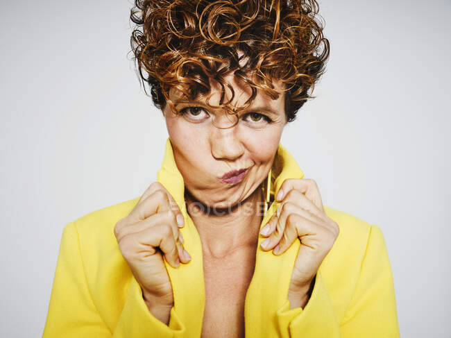 Trendy adult woman with curly hair adjusting collar of yellow coat and looking at camera with arrogant face against yellow background — Stock Photo