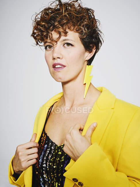 Portrait de femme gaie avec haut à paillettes et boucle d'oreille éclair souriant et ajustant manteau jaune élégant sur fond gris — Photo de stock