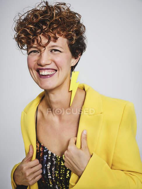 Ritratto di donna allegra con la parte superiore di paillettes e orecchino fulmine sorridente e regolazione elegante cappotto giallo su sfondo grigio — Foto stock