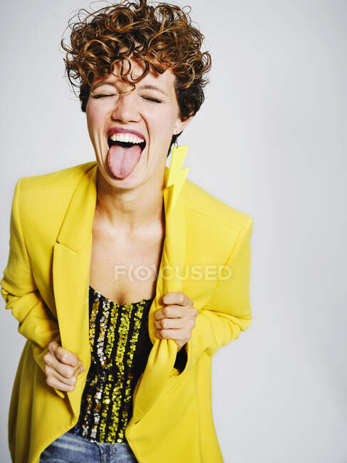 Funny adult female in stylish outfit closing eyes and showing tongue to camera against gray background — Stock Photo