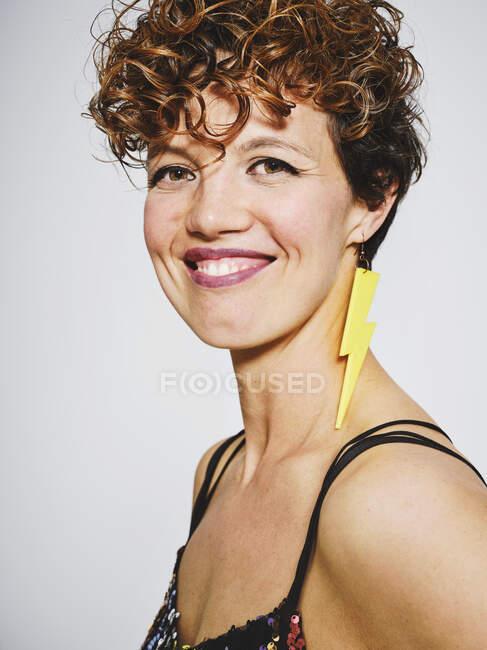 Ritratto di donna allegra con la parte superiore di paillettes e orecchino fulmine sorridente alla macchina fotografica mentre in piedi su sfondo grigio — Foto stock