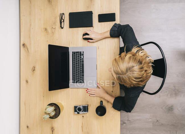 Vue du dessus de la femme au bureau en bois avec ordinateur portable, ordinateur portable, portable et appareil photo. — Photo de stock