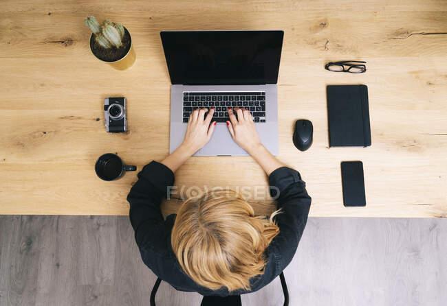 Visão superior da mulher na mesa de madeira com laptop, notebook, notebook de telefone celular e câmera de fotos. — Fotografia de Stock