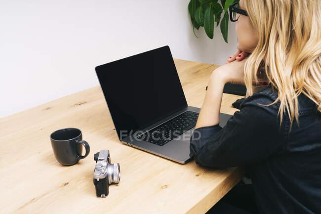 Hermosa mujer rubia caucásica trabaja desde su sala de estar con su computadora portátil en un escritorio de madera. Ella usa ropa casual negra. - foto de stock