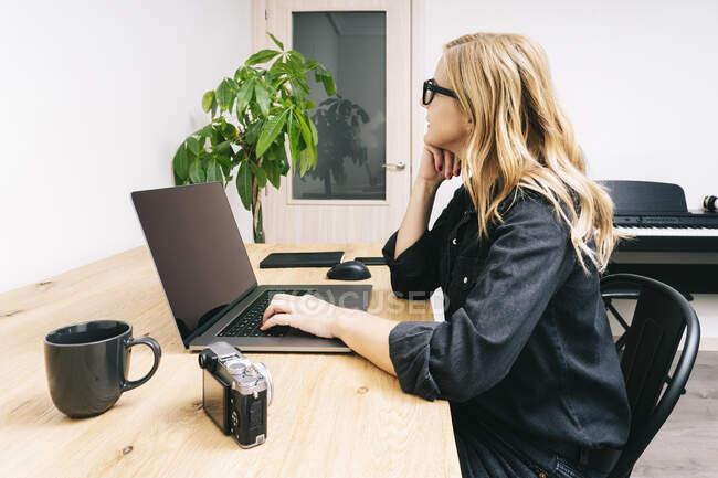 Die schöne blonde Kaukasierin arbeitet von ihrem Wohnzimmer aus mit ihrem Laptop auf einem Holztisch. Sie trägt schwarze Freizeitkleidung. — Stockfoto
