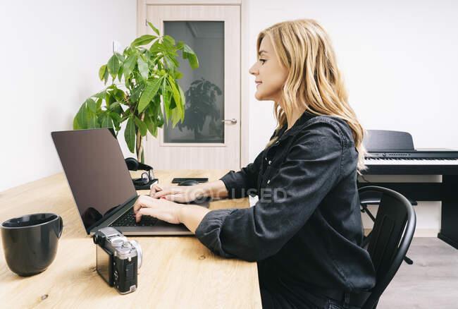 Bella donna caucasica bionda lavora dal suo soggiorno con il suo computer portatile su una scrivania di legno. Indossa abiti casual neri.. — Foto stock