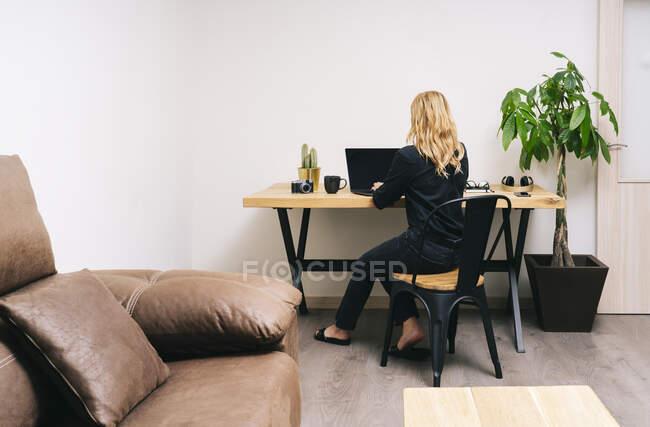 Прекрасна білявка Кавказька працює зі своєї вітальні з ноутбуком на дерев'яному столі. Вона носить чорний повсякденний одяг.. — стокове фото