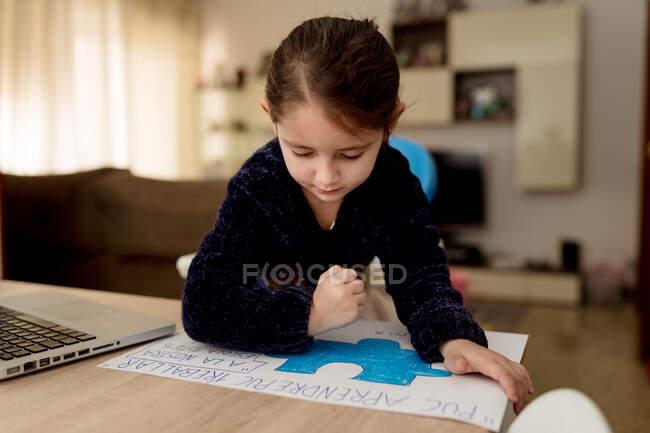 Заколдованная маленькая девочка рисует креативный баннер, сидя за столом с ноутбуком в уютной комнате дома — стоковое фото