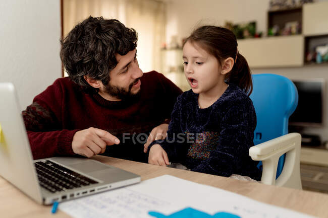 Bearded adult man sitting near little girl with laptop and helping daughter with remote education while staying at home together — Stock Photo
