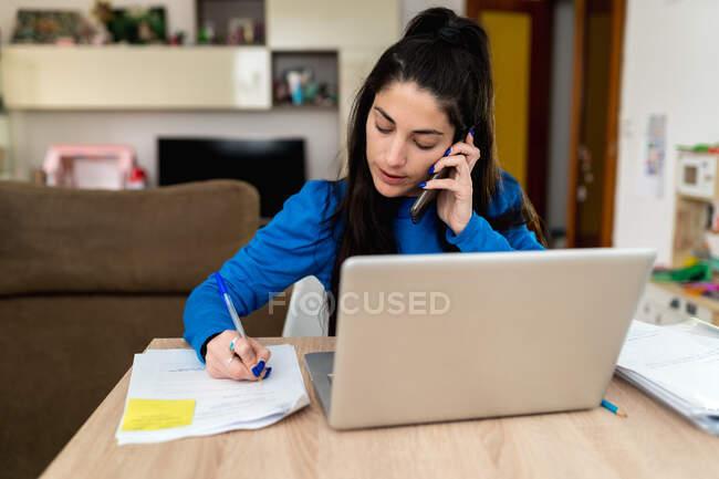 Mujer morena tomando notas con pluma mientras responde a una llamada telefónica sentada en la mesa con el ordenador portátil y trabajando en un proyecto remoto en casa — Stock Photo