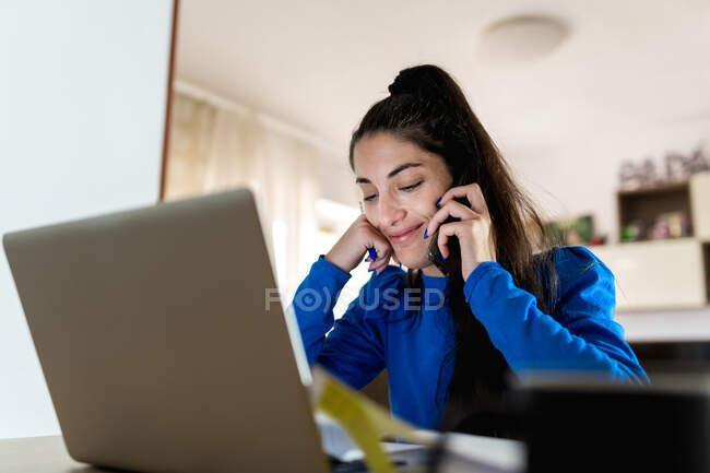 Mujer adulta feliz contestando una llamada telefónica sentada en la mesa con el ordenador portátil y trabajando en un proyecto remoto en casa — Stock Photo