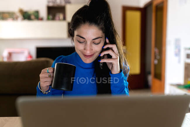Happy adult woman holding a cup of coffee while answering a phone call sitting at table with laptop and working on remote project at home — Stock Photo