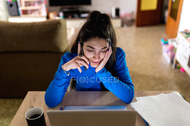 Happy adult woman answering a phone call sitting at table with laptop and working on remote project at home — Stock Photo