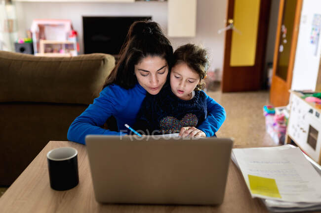 Busy woman hugging little girl and reading papers while sitting at table with laptop and working on freelance project at home — Stock Photo
