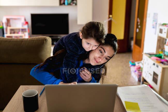 Femme adulte avec une petite fille sur le dos étreignant à l'aide d'un ordinateur portable et essayant de faire un projet indépendant tout en jouant avec sa fille et en travaillant à la maison — Photo de stock