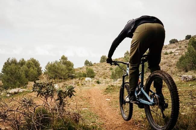 Цикліст їде на велосипеді по скелястій стежці лісу. — стокове фото