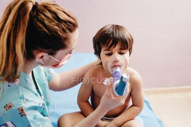 Vista lateral de la joven pediatra en máscara médica haciendo tratamiento por inhalación con nebulizador para niños pequeños con problemas respiratorios en el hospital - foto de stock
