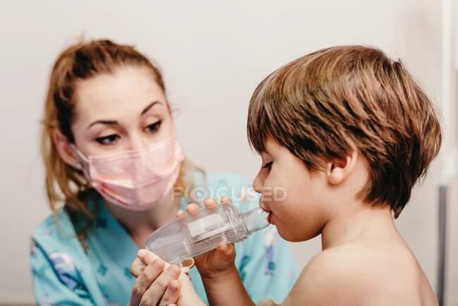 Criança usando inalador na clínica durante o check-up — Fotografia de Stock