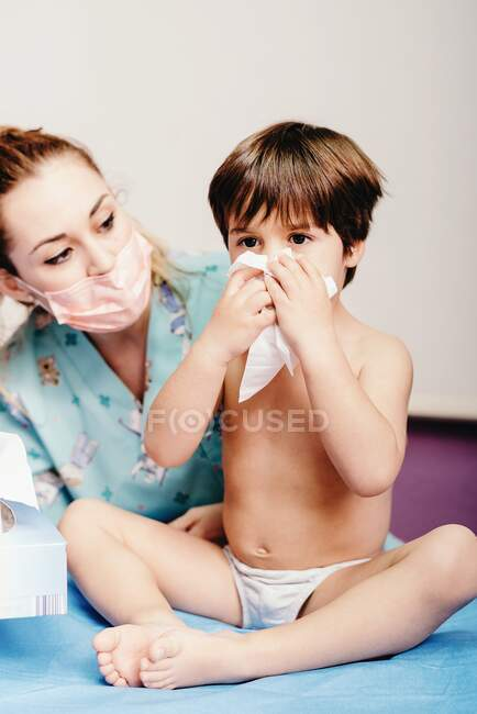 Niño enfermo sonándose la nariz mientras está sentado en la cama del hospital con una enfermera parada cerca - foto de stock