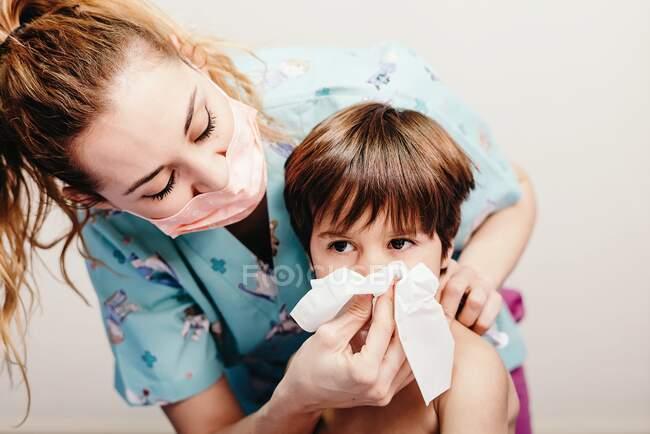 Niño sonándose la nariz en el hospital en revisión - foto de stock