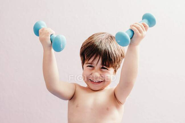 Cheerful little boy with dumbbells — Stock Photo