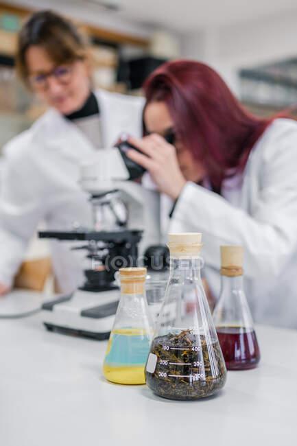 Femme utilisant un microscope près de collègues en laboratoire — Photo de stock