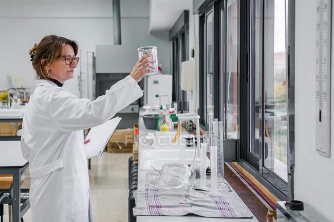 Chimiste mature menant une expérience en laboratoire — Photo de stock