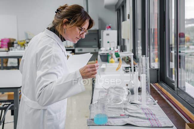 Vue latérale du scientifique femelle mature avec presse-papiers examinant la verrerie tout en travaillant dans un laboratoire de chimie moderne — Photo de stock