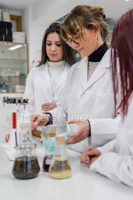Femme mûre en manteau blanc montrant une expérience chimique avec du liquide à de jeunes femmes stagiaires tout en travaillant dans un laboratoire contemporain — Photo de stock
