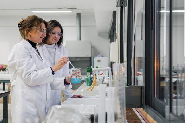 Cheerful teacher and student conducting experiment in lab — Stock Photo