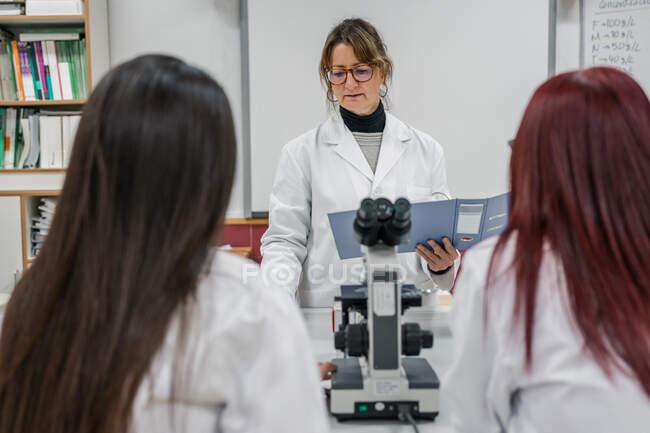 Femme mûre enseignant des étudiants en laboratoire — Photo de stock
