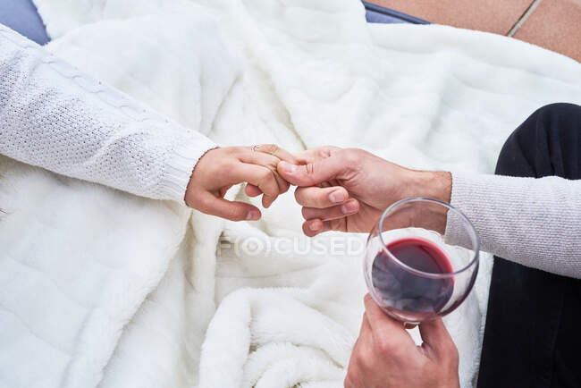 From above side view of cheerful young couple in casual wear toasting with glasses of red wine while enjoying happy moments together — Stock Photo