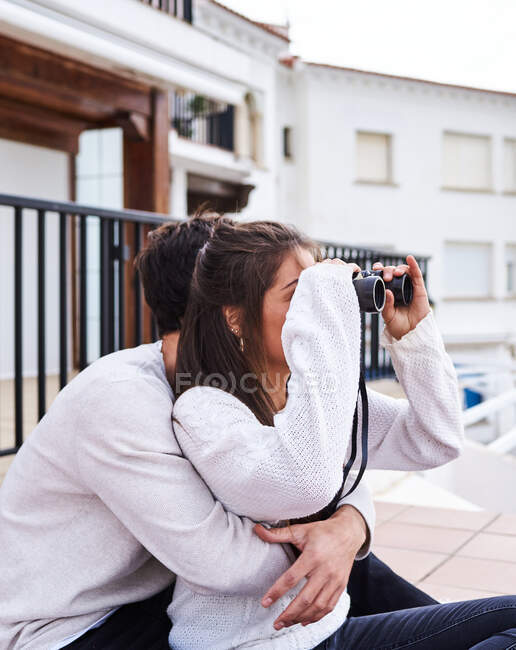 Side view of cheerful romantic couple in casual wear sitting on terrace with binoculars and enjoying view while spending holidays together at seaside — Stock Photo