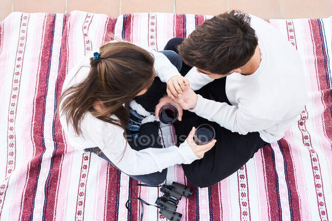 From above side view of affectionate tender young couple hugging and kissing while having romantic moments together — Stock Photo