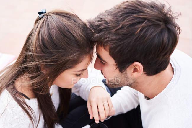 De dessus vue latérale d'affectueux jeune couple tendre embrassant et embrassant tout en ayant des moments romantiques ensemble — Photo de stock