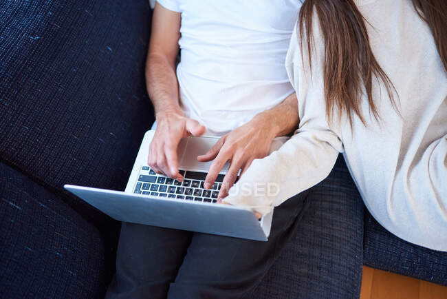 High angle of young man browsing laptop and woman reading interesting book while resting together on comfortable couch in modern living room — Stock Photo