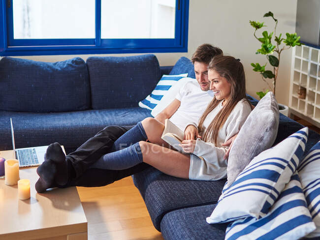 Side view of cheerful young husband and wife in casual wear sitting on couch with laptop and book while spending weekend together at home — Stock Photo