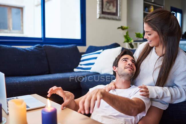 Positive junge Frau umarmt glücklichen Mann, während er auf dem Sofa im gemütlichen Wohnzimmer sitzt — Stockfoto
