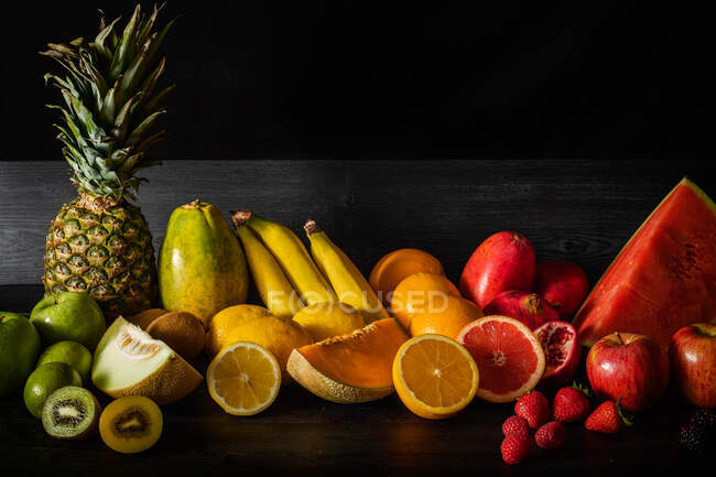 Куча различных свежих фруктов, полных витаминов, помещенных на черном столе пиломатериалов — стоковое фото