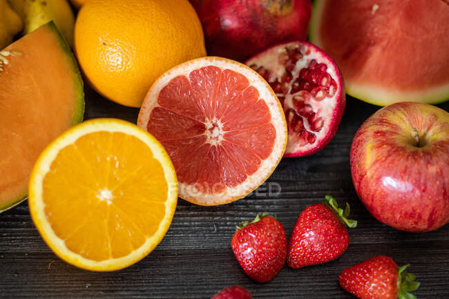 From above bunch of various fresh fruits full of vitamins placed on black lumber table — Foto stock
