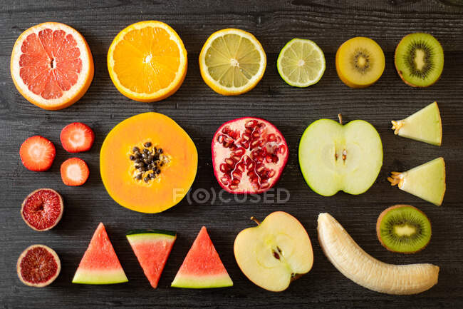 Вид сверху на различные очищенные и срезанные здоровые фрукты и овощи, расположенные на черном светлом столе — стоковое фото