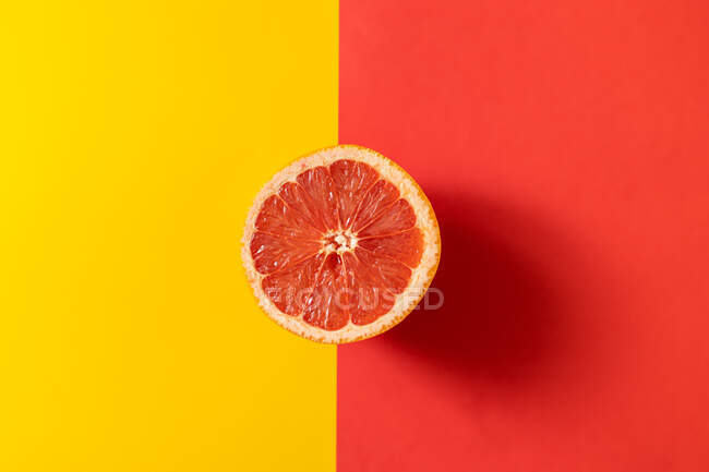 Top view of half of ripe grapefruit placed on line between yellow and red backgrounds — Stock Photo