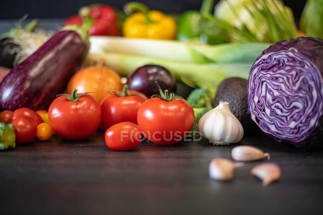 Montón de verduras frescas surtidos colocados en la mesa negra durante la preparación de alimentos saludables en la cocina - foto de stock
