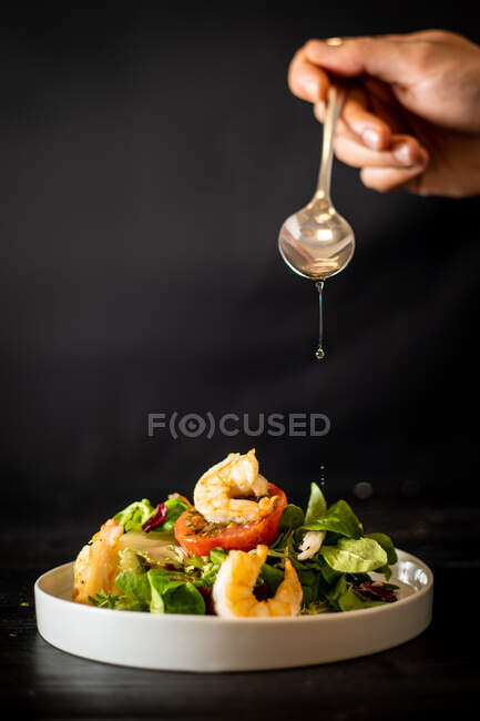 Unrecognizable cook adding spoonful of oil to yummy vegetable salad with shrimps on black background — Stock Photo