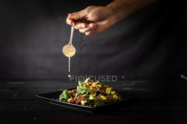 Unrecognizable cook adding spoonful of sauce into a yummy portion of palatable avocado salad with fresh spinach and walnuts served on square black plate on cafe table — Stock Photo