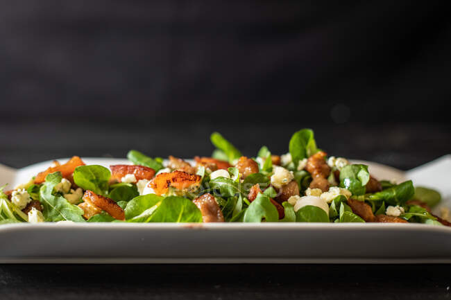 From above healthy spinach salad with tomatoes and mushrooms on black background — Stock Photo
